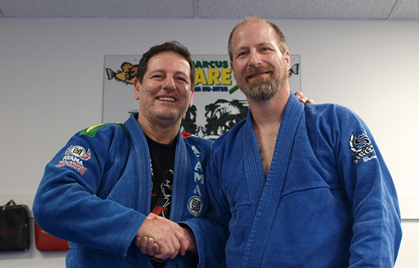 Two men are shaking hands and smiling. The man on the right, Marcus Soares, has an arm around the other man's shoulders. The man on the left, Bryan Rumble, is partially bald with facial hair.
