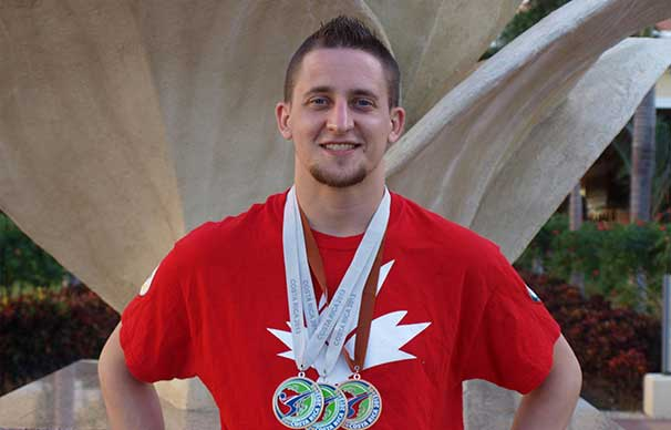 A man stands in front of a statue, he has a smile on his face and two silver medals and a bronze one around his neck.