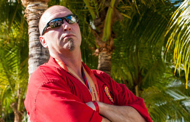 Darrell Warren, a bald man with facial hair and sunglasses stands with his arms crossed in front of palm trees. He looks serious but seems to be fighting a smile.