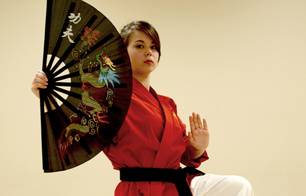 A young woman in her early 20s has a serious expression as she poses with a decorative fan. Her hair is pulled back and her left hand is raised palm out as her left hand holds the fan.