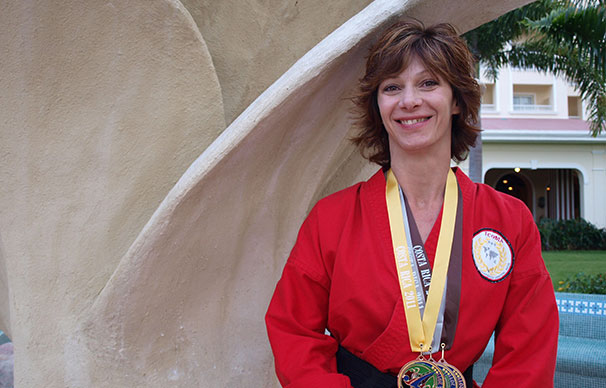 A woman with short cropped hair is smiling. She has a gold, silver and bronze medal around her neck. There are palm trees in the background.